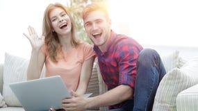 Счастливый смеяться над пар, сидя на кресле перед открытой компьтер-книжкой Стоковое Фото