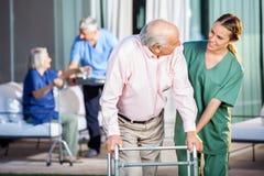 Счастливый смотритель помогая старшему человеку в использовании стоковая фотография