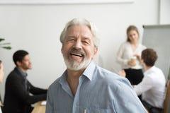 Счастливый старший бизнесмен смеясь над смотрящ камеру в офисе, p Стоковые Изображения