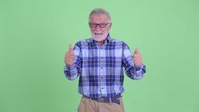 Счастливый старший бородатый человек хипстера давая большие пальцы руки вверх и выглядя возбужденный акции видеоматериалы