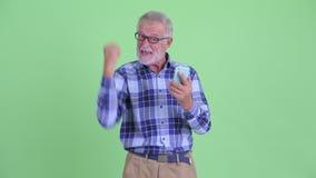 Счастливый старший бородатый человек хипстера используя телефон и хорошие новости получать сток-видео