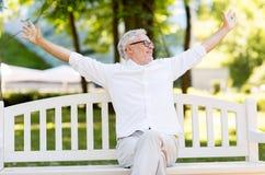 Счастливый старший человек сидя на стенде на парке лета стоковые изображения