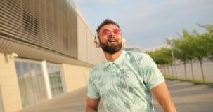 Счастливый стильный расслабленный африканский человек в розовых солнечных очках наслаждается музыкой в наушниках и танцуется окол акции видеоматериалы