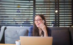 Счастливый студент женщины имея телефонный разговор клетки после работы на портативной сет-книге Стоковое Фото