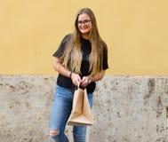 Счастливый с бумажным мешком повторно использованным на желтой предпосылке стоковые фото
