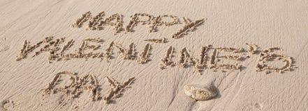 Счастливый текст дня Валентайн написанный на песке стоковые изображения