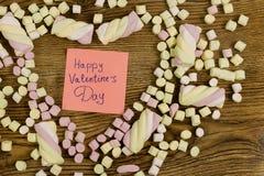 Счастливый текст дня ` s валентинки украшенный с зефирами в форме сердца концепция влюбленности на деревянном Стоковое фото RF