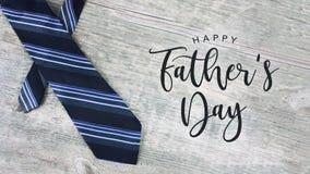 Счастливый текст дня ` s отца с Striped связью над деревянной предпосылкой Стоковое фото RF