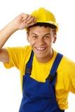 счастливый трудный шлем его с усмешки принимая работника Стоковая Фотография