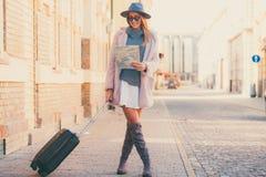 Счастливый турист женщины с исследуя картой и багажом пока дежурный стоковое фото rf
