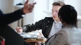 Счастливый тысячелетний мужской менеджер в стильных eyeglasses говоря с многонациональными коллегами на удобном светлом ультрамод акции видеоматериалы