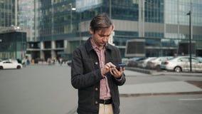 Счастливый усмехаясь бизнесмен используя современный smartphone около офиса на раннем утре, успешный работодатель для того чтобы  видеоматериал