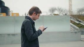 Счастливый усмехаясь бизнесмен используя современный smartphone около офиса на раннем утре, успешный работодатель для того чтобы  акции видеоматериалы