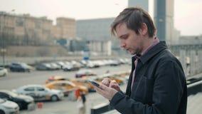 Счастливый усмехаясь бизнесмен используя современный smartphone около офиса на раннем утре, успешный работодатель для того чтобы  сток-видео