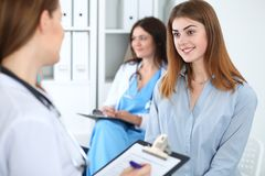 Счастливый усмехаясь женский пациент с ее доктором на клинике или больнице Концепция медицины и здравоохранения стоковое изображение