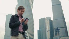 Счастливый усмехаясь костюм бизнесмена нося и использование современного smartphone около офиса на раннем утре, успешного работод сток-видео