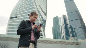 Счастливый усмехаясь костюм бизнесмена нося и использование современного smartphone около офиса на раннем утре, успешного работод видеоматериал