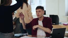Счастливый усмехаясь молодой европейский мужской коммерческий директор показывая жестами, говорящ с женским боссом на современном сток-видео