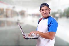 Счастливый усмехаясь молодой мужской азиатский студент с компьтер-книжкой Стоковые Фотографии RF