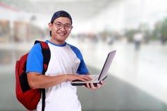 Счастливый усмехаясь молодой мужской азиатский студент с компьтер-книжкой Стоковое фото RF