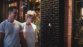 Счастливый усмехаясь молодой человек и женщина держат руки наслаждаясь датой, идя и говоря вдоль улицы вечера в Soho, Нью-Йорке акции видеоматериалы