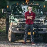 Счастливый усмехаясь молодой человек фермера стоя перед грузовым пикапом готовым для работы стоковое изображение