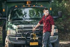 Счастливый усмехаясь молодой человек фермера стоя перед грузовым пикапом готовым для работы стоковое изображение rf