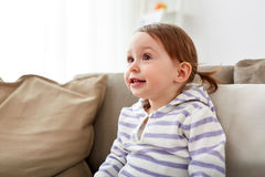 Счастливый усмехаясь ребёнок сидя на софе дома Стоковые Изображения