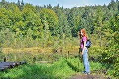 Счастливый усмехаясь рыжеволосый hiker девушки с рюкзаком и ручкой в горах около мертвого озера в прикарпатских горах стоковое изображение rf