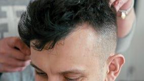 Счастливый усмехаясь человек в парикмахерскае Парикмахер работает с клипером в салоне парикмахерских услуг акции видеоматериалы