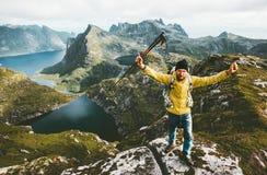 Счастливый успех человека путешественника поднял руки стоя на верхней части горы Стоковое Изображение