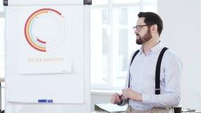 Счастливый успешный молодой усмехаясь бизнесмен представляя диаграмму продаж на flipchart к работникам на современной встрече офи видеоматериал