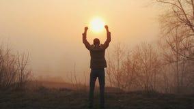 Счастливый успешный человек празднуя во время восхода солнца или захода солнца Счастливый и свободный Гай поднимает его руки и ра сток-видео