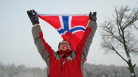 Счастливый флаг владениями болельщика человека Норвегии развевая в ветре видеоматериал