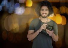 счастливый фотограф с камерой на руках на ноче Запачканные синь и желтый цвет освещают позади и перекрытие Стоковые Фотографии RF