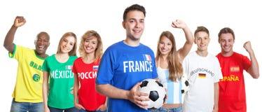 Счастливый французский поклонник футбола с шариком и вентиляторы от других стран стоковые изображения rf