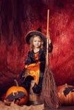 Счастливый хеллоуин! красивая маленькая девочка в костюме ведьмы с mag Стоковые Изображения RF