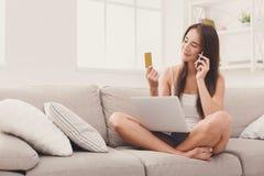 Счастливый ходить по магазинам женщины онлайн с кредитной карточкой Стоковая Фотография