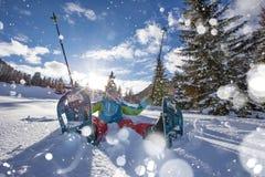 Счастливый ходок snowshoe в снеге порошка с красивым солнцем излучает стоковые изображения rf