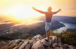 Счастливый человек в горах смотря заход солнца стоковые изображения rf