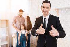 Счастливый человек в костюме показывает большие пальцы руки вверх расквартируйте сбывание Молодая семья смотрит квартиры стоковые изображения rf