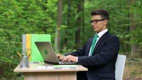 Счастливый человек в работе делового костюма заканчивая и ослаблять в зеленом красивом лесе сток-видео