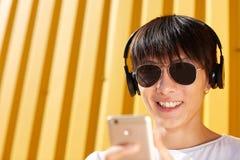 Счастливый человек в солнечных очках с телефоном на желтой предпосылке Принципиальная схема прогресса скопируйте космос стоковые изображения rf