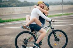 Счастливый человек давая подруге подъем на его поперечину велосипеда на пляже Стоковая Фотография