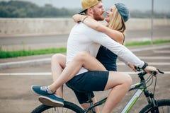 Счастливый человек давая подруге подъем на его поперечину велосипеда на пляже Стоковые Фото