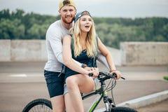 Счастливый человек давая подруге подъем на его поперечину велосипеда на пляже Стоковое Изображение RF