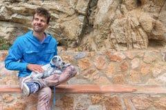 Счастливый человек счастливый держащ его принятого смешанного далматинского щенка и сидящ на каменном стенде Концепция принятия л стоковое фото rf