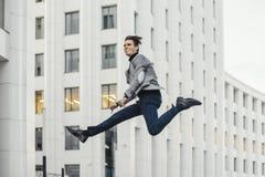 Счастливый человек идя к или от работы и танцуя рядом с деловым центром стоковые изображения