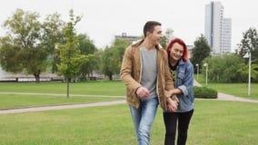 Счастливый человек и женщина держа руки и идя в парк города видеоматериал
