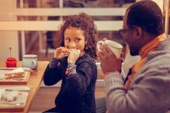 Счастливый человек наблюдая, как его милая дочь съела сэндвич стоковое фото